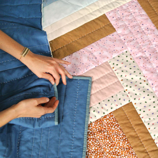 Hand sewing the binding on the Weekend Candy Spring Flowers quilt