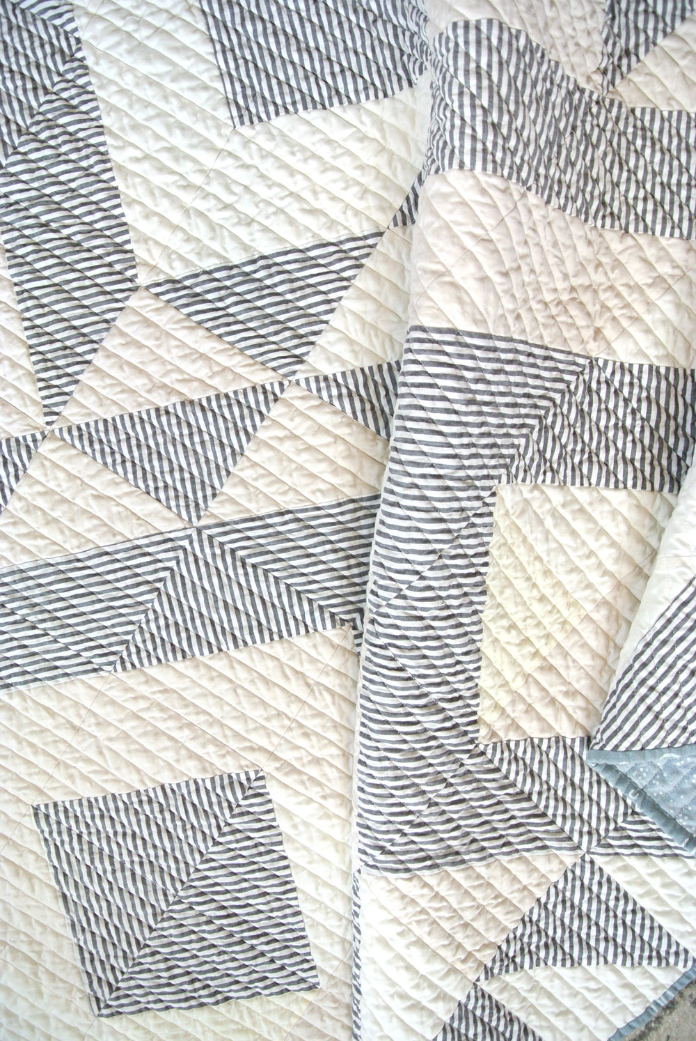 The crinkled straight line quilting on this Triangle Jitters quilt shows what fabric looks like after it is washed