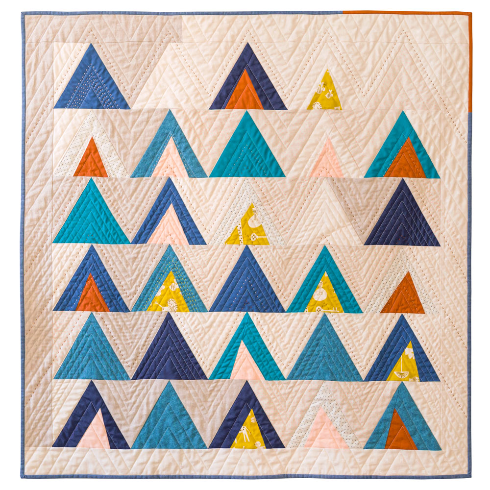 The Mod Mountains quilt pattern is fat quarter friendly and great for using fabric scraps from your stash. A video tutorial show step by step how to sew triangles. This quilt pattern includes fabric requirements for queen/full, twin, throw and baby quilt sizes. | Suzy Quilts