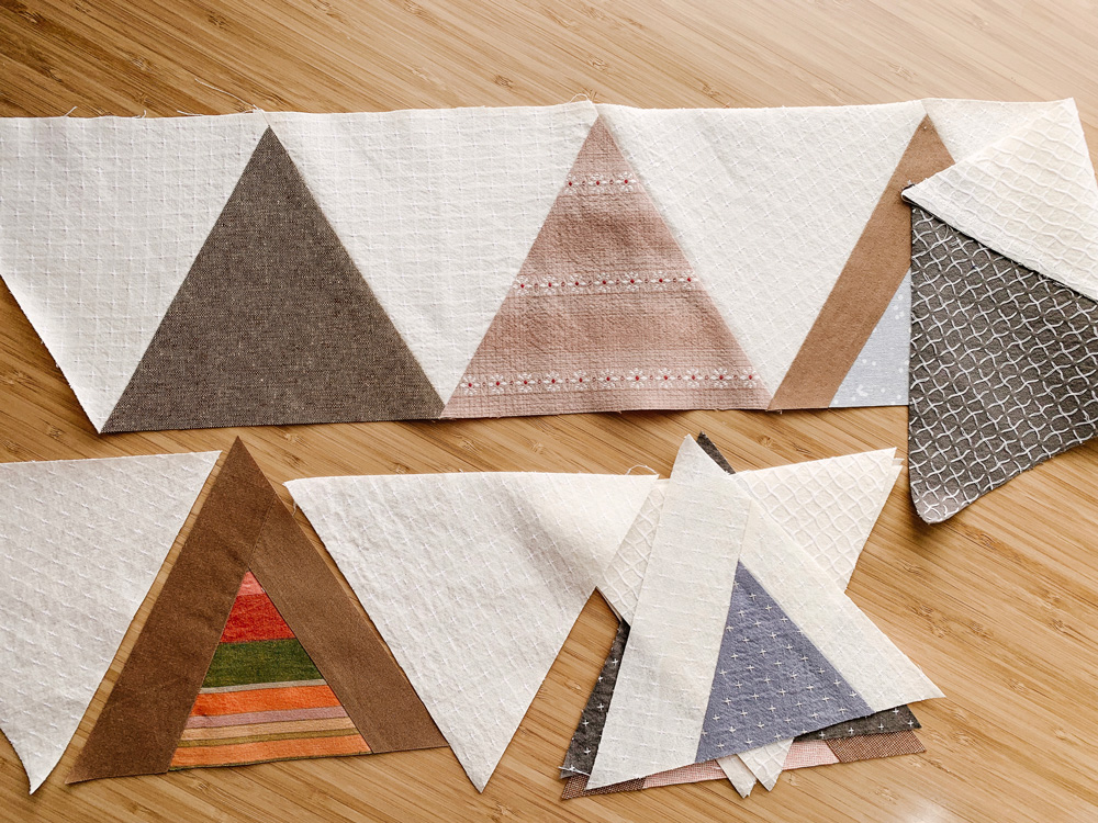 The Mod Mountains quilt pattern is fat quarter friendly and great for using fabric scraps from your stash. Video tutorials show step by step how to cut templates and sew triangles.
