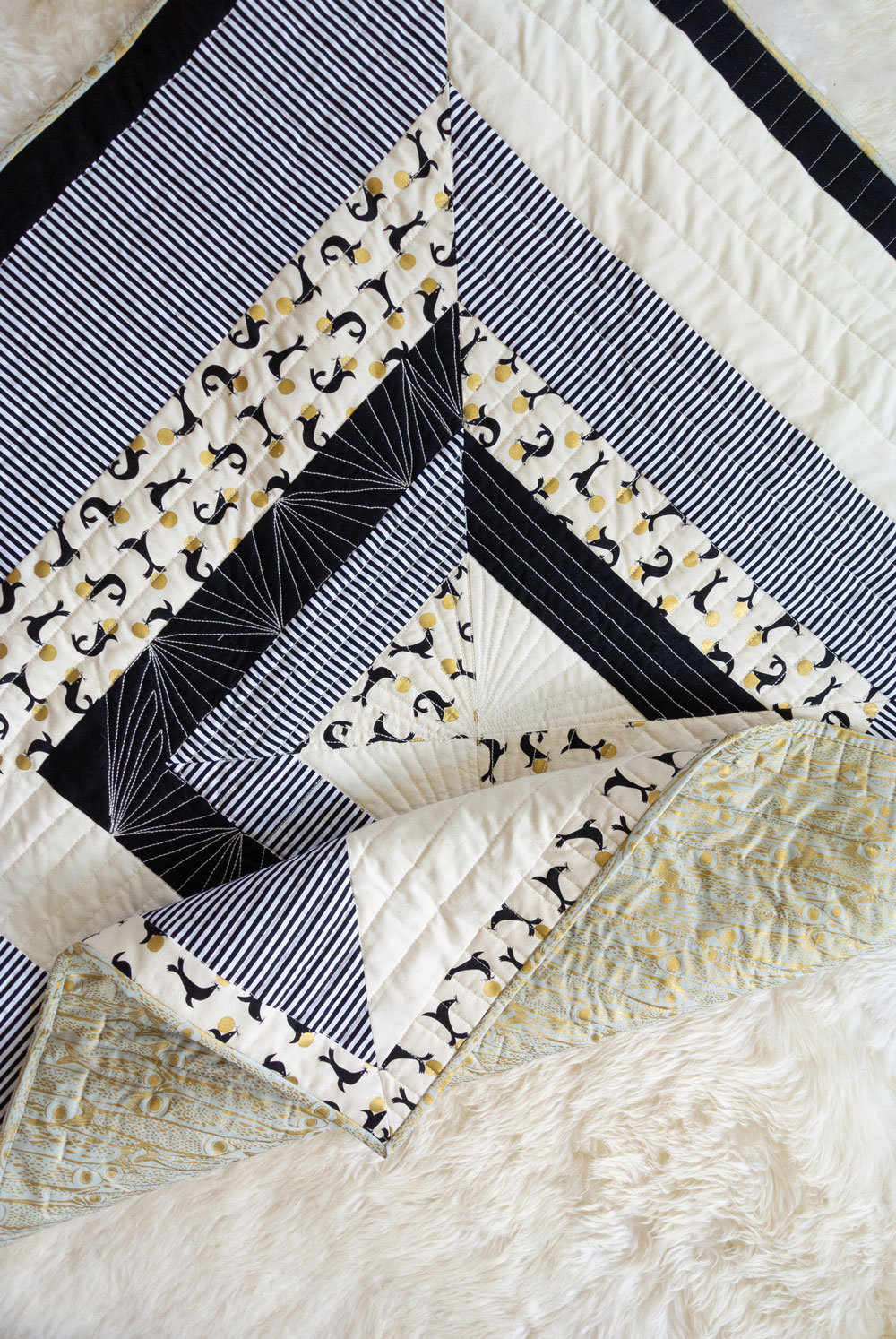 The Reflections quilt pattern is a beginner-friendly modern design that includes king, queen, full, twin, throw and baby quilt sizes. This is a fast and fun baby quilt pattern that plays on symmetry and high contrast!