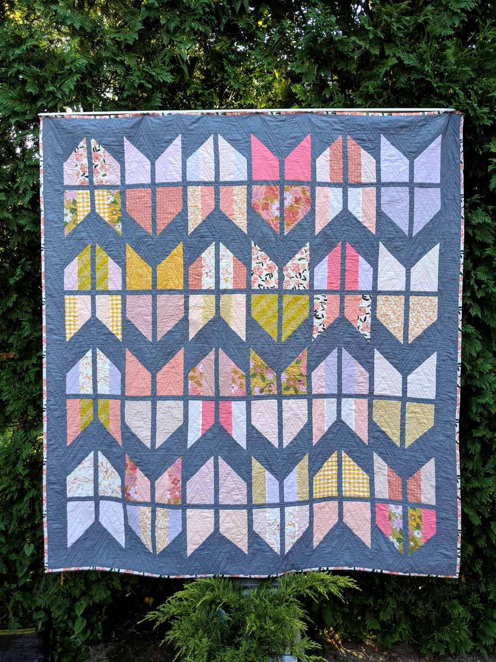 The Tail Feather Quilt Pattern is a modern quilt design that is fat quarter friendly! This PDF digital download includes queen, twin, throw and baby quilt sizes. A great beginner quilt pattern! SuzyQuilts.com #quiltpattern