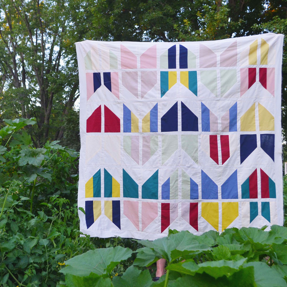The Tail Feather quilt pattern is a bold, modern design that is fat quarter friendly. It comes in baby, throw, twin, and queen sizes. Beginner friendly! SUZY QUILTS #quiltpattern #modernquiltpattern