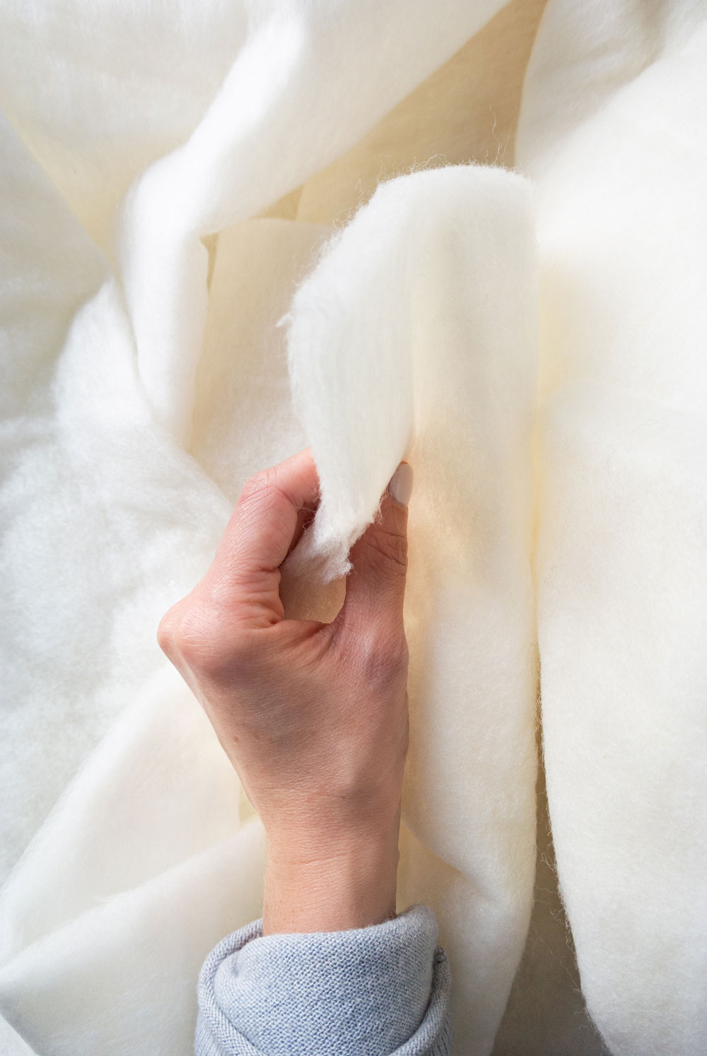 Why wool batting makes the warmest quilts! Learn how to quilt with this beautifully fluffy and sustainable fiber. suzyquilts.com #quilting #quilttutorial