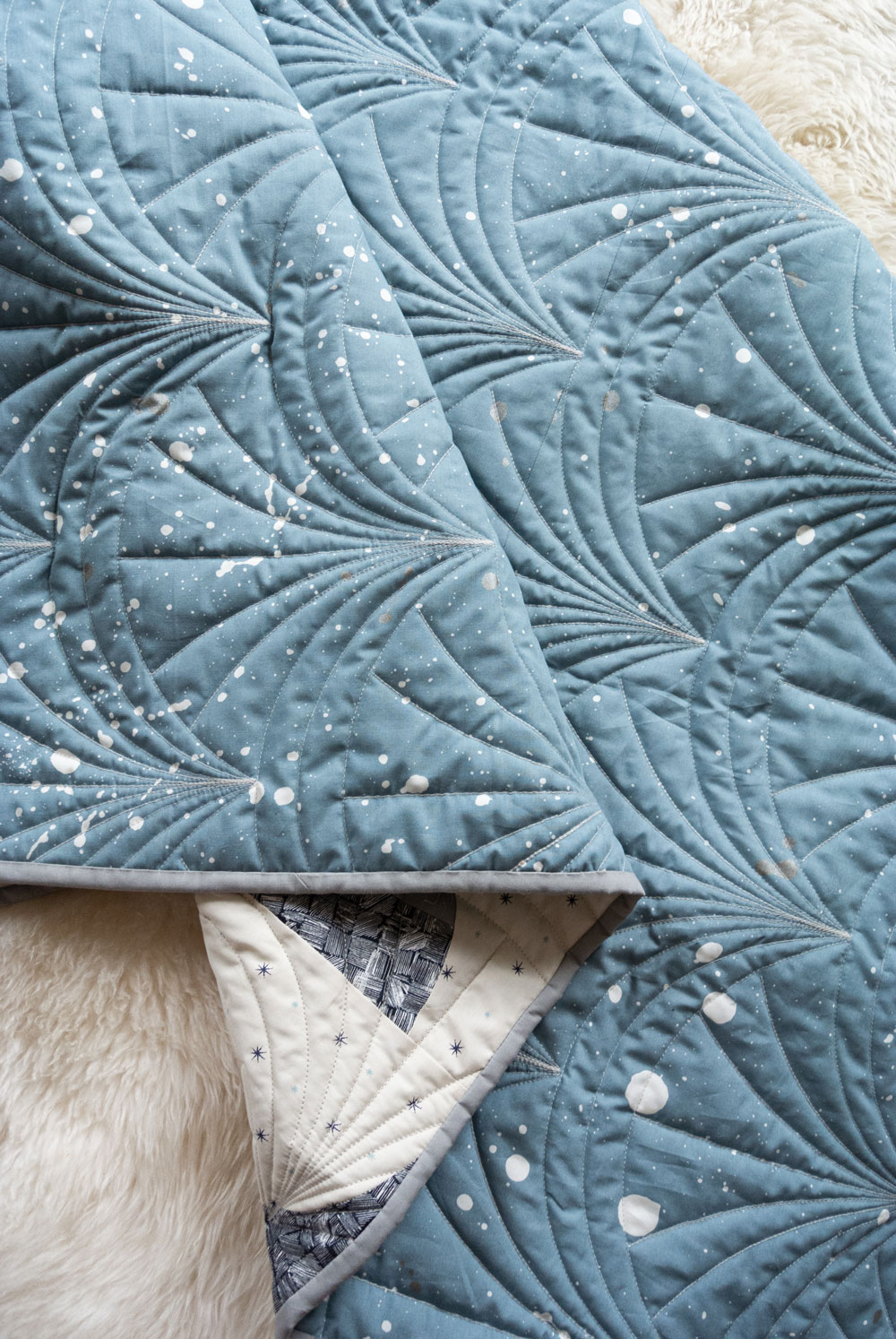 This Great Gatsby inspired Modern Fans quilt kit uses icy blues, grays and metallic silver fabric to bring elegance and pizzazz to a cozy quilt. suzyquilts.com #quiltpattern #quilt #modernquiltpattern