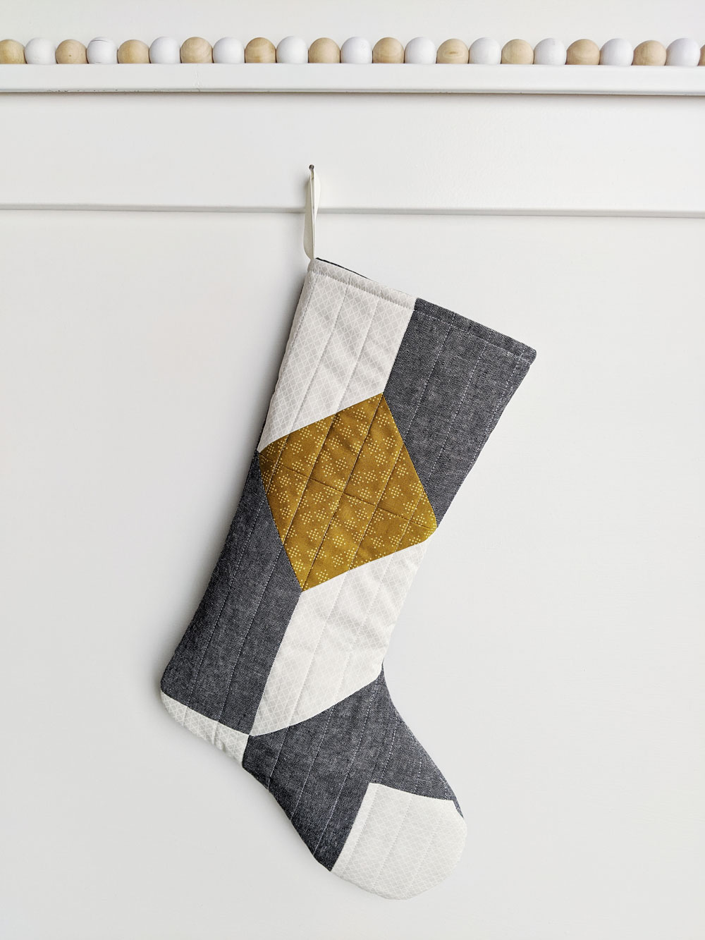 A free quilted Christmas stocking pattern right in time for the holidays! Sew a simple, modern stocking with this step by step tutorial. suzyquilts.com #DIYstocking #quilttutorial