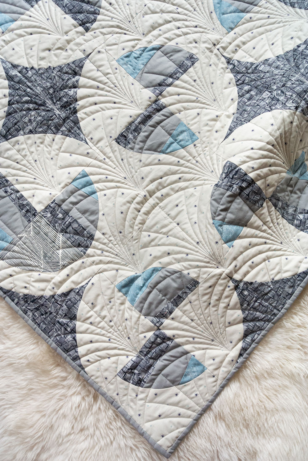 This Great Gatsby inspired Modern Fans quilt kit uses icy blues, grays and metallic silver fabric to bring elegance and pizzazz to a cozy quilt. suzyquilts.com #artdeco