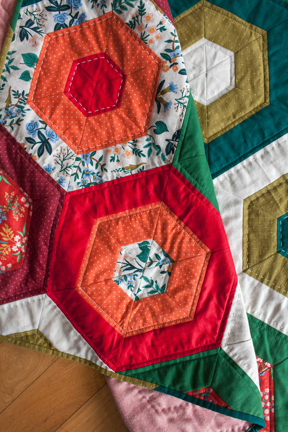 It's easy to get in the holiday spirit and get your Christmas quilting done with a pattern like Hexie Stripe. It's a vintage design with a modern twist! To make a throw all you need are 9 different 1/2 yd. cuts of fabric. Mix red and green solids with some floral prints for a beautifully festive quilt! suzyquilts.com #christmasquilt #hexiequilt
