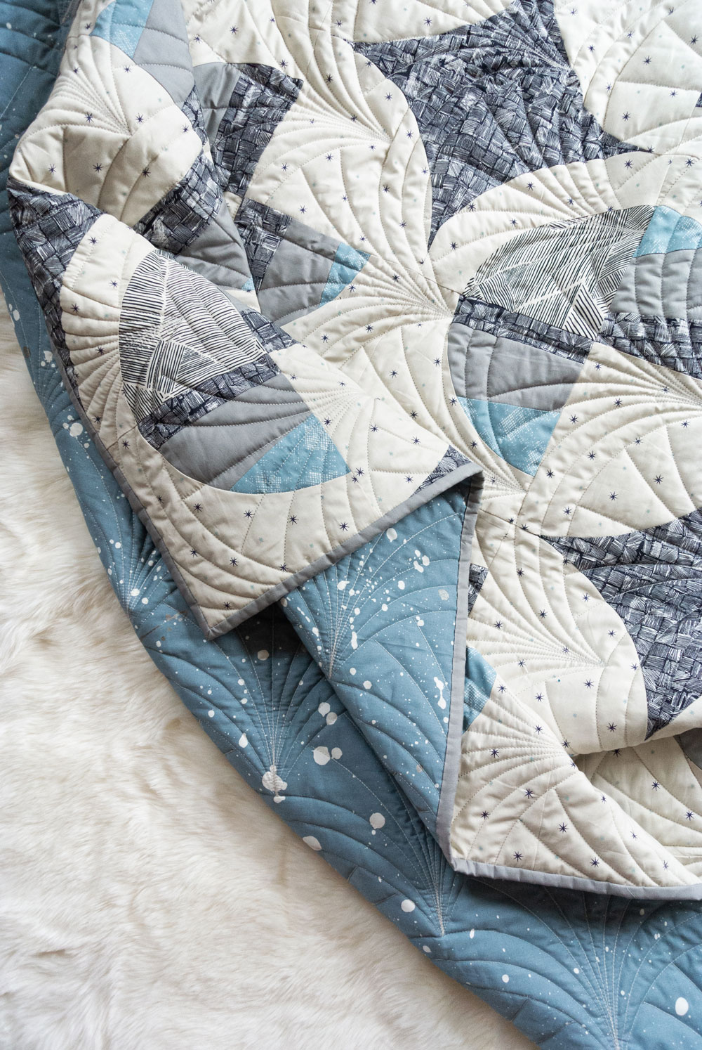 This Great Gatsby inspired Modern Fans quilt kit uses icy blues, grays and metallic silver fabric to bring elegance and pizzazz to a cozy quilt. suzyquilts.com #quiltpattern #quilt #modernquilt