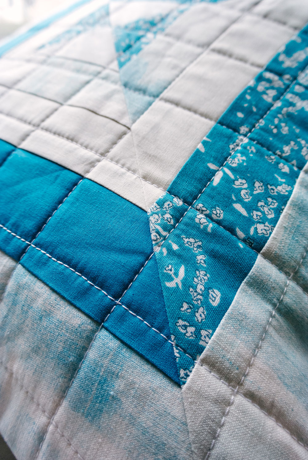 The Reflections pillow is a very fast project that is perfect for using scraps of fabric! This modern quilt pattern includes instructions for an 18-inch pillow and a 30-inch wall hanging. suzyquilts.com #pillowtutorial