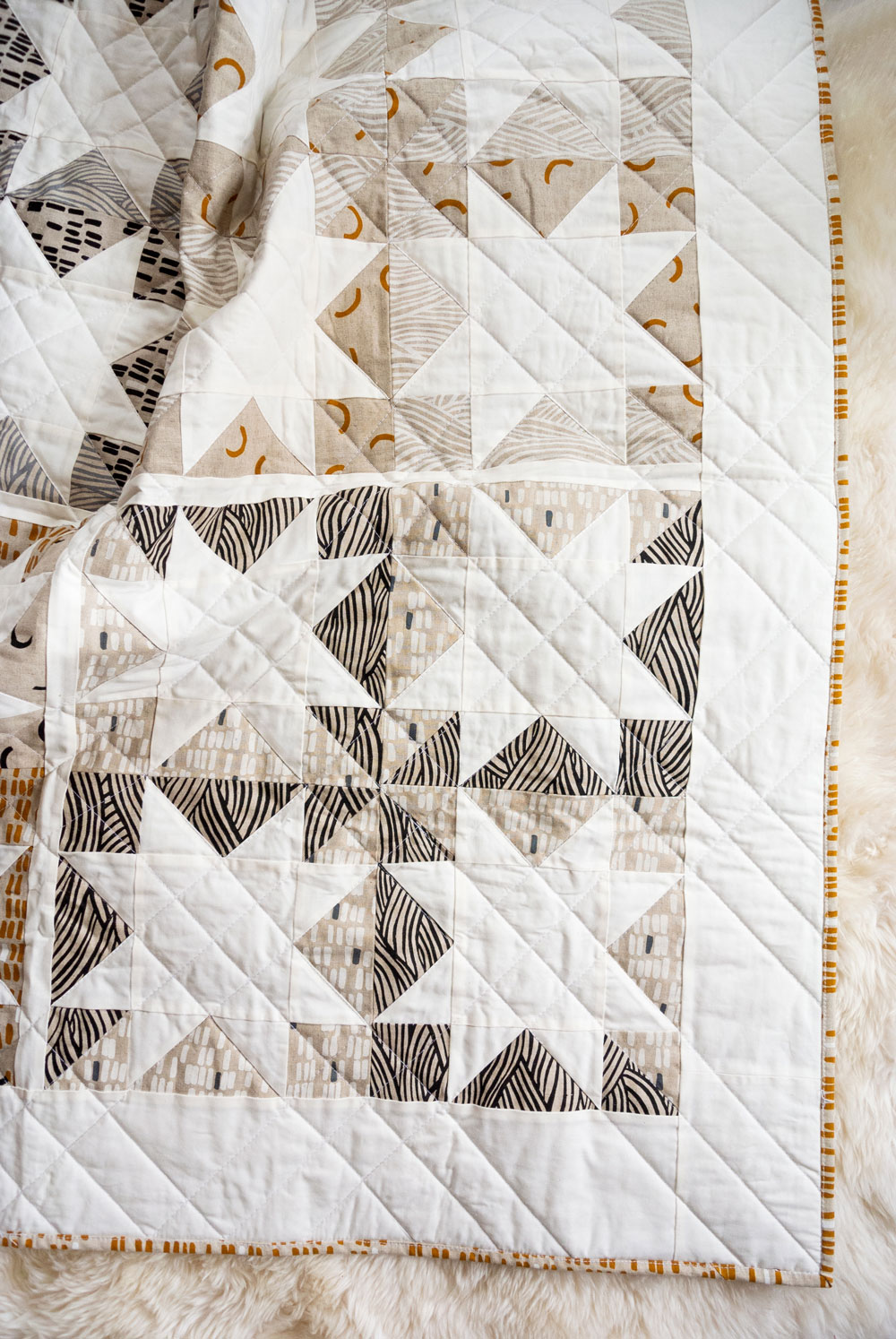 Make a sophisticated, neutral quilt using the Stars Hollow quilt pattern. This is a classic quilt pattern, but with a modern twist. The design plays on negative space to create traditional sawtooth star quilt blocks. suzyquilts.com #linen #quilting