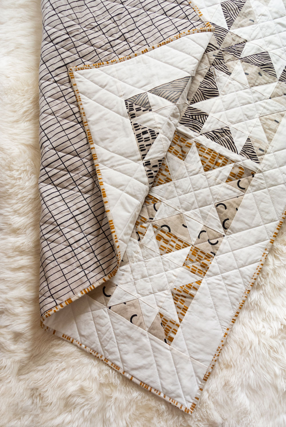 Make a sophisticated, neutral quilt using the Stars Hollow quilt pattern. This is a classic quilt pattern, but with a modern twist. The design plays on negative space to create traditional sawtooth star quilt blocks. suzyquilts.com #linen #quiltpattern