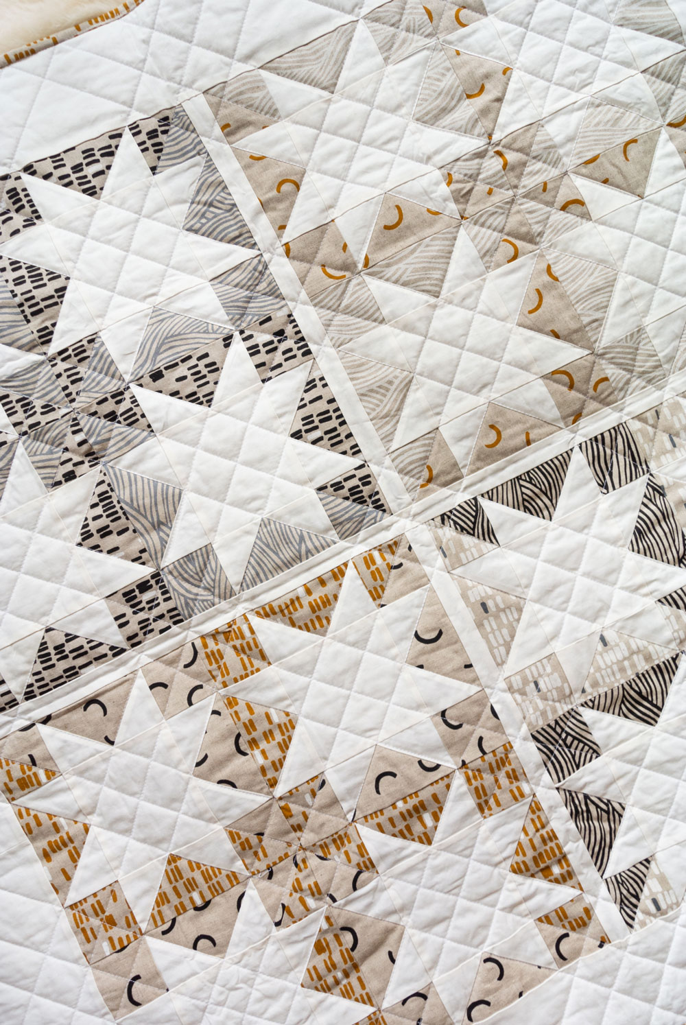 Make a sophisticated, neutral quilt using the Stars Hollow quilt pattern. This is a classic quilt pattern, but with a modern twist. The design plays on negative space to create traditional sawtooth star quilt blocks. suzyquilts.com #homedecor #quiltpattern