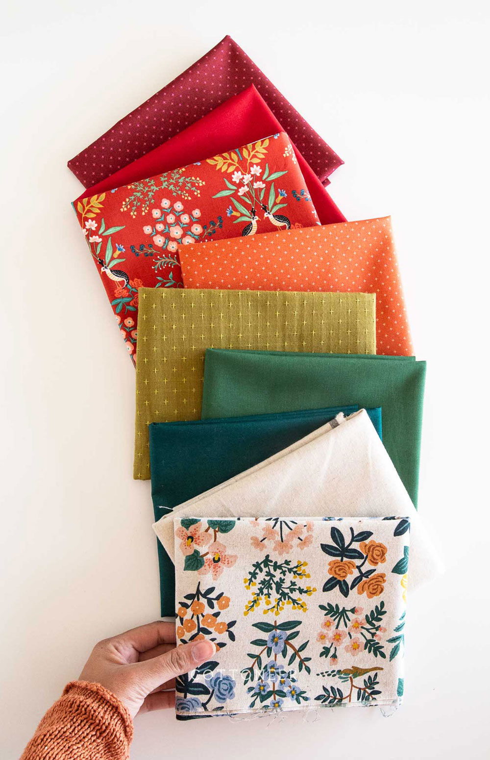 It's easy to get in the holiday spirit and get your Christmas quilting done with a pattern like Hexie Stripe. It's a vintage design with a modern twist! To make a throw all you need are 9 different 1/2 yd. cuts of fabric. Mix red and green solids with some floral prints for a beautifully festive quilt! suzyquilts.com #christmasquilt #christmasfabric