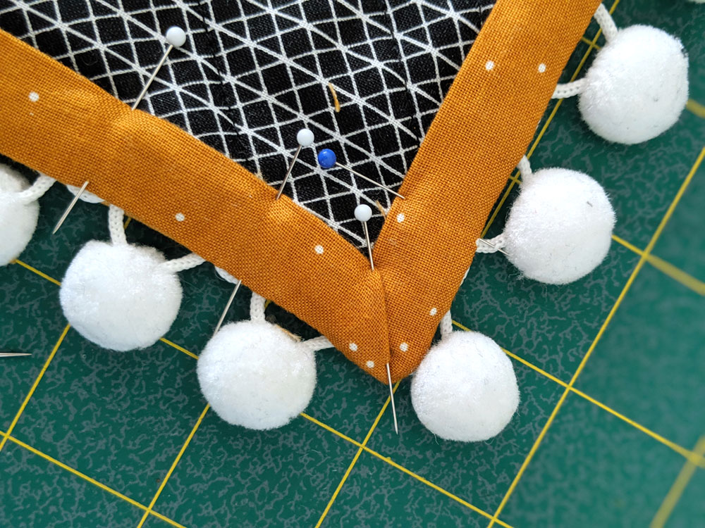 This DIY tutorial will show you step by step how to sew pom pom trim to a quilt. Make your next quilt extra special with this easy sewing tutorial | suzyquilts.com #quiltingtutorial #sewpompomtrim