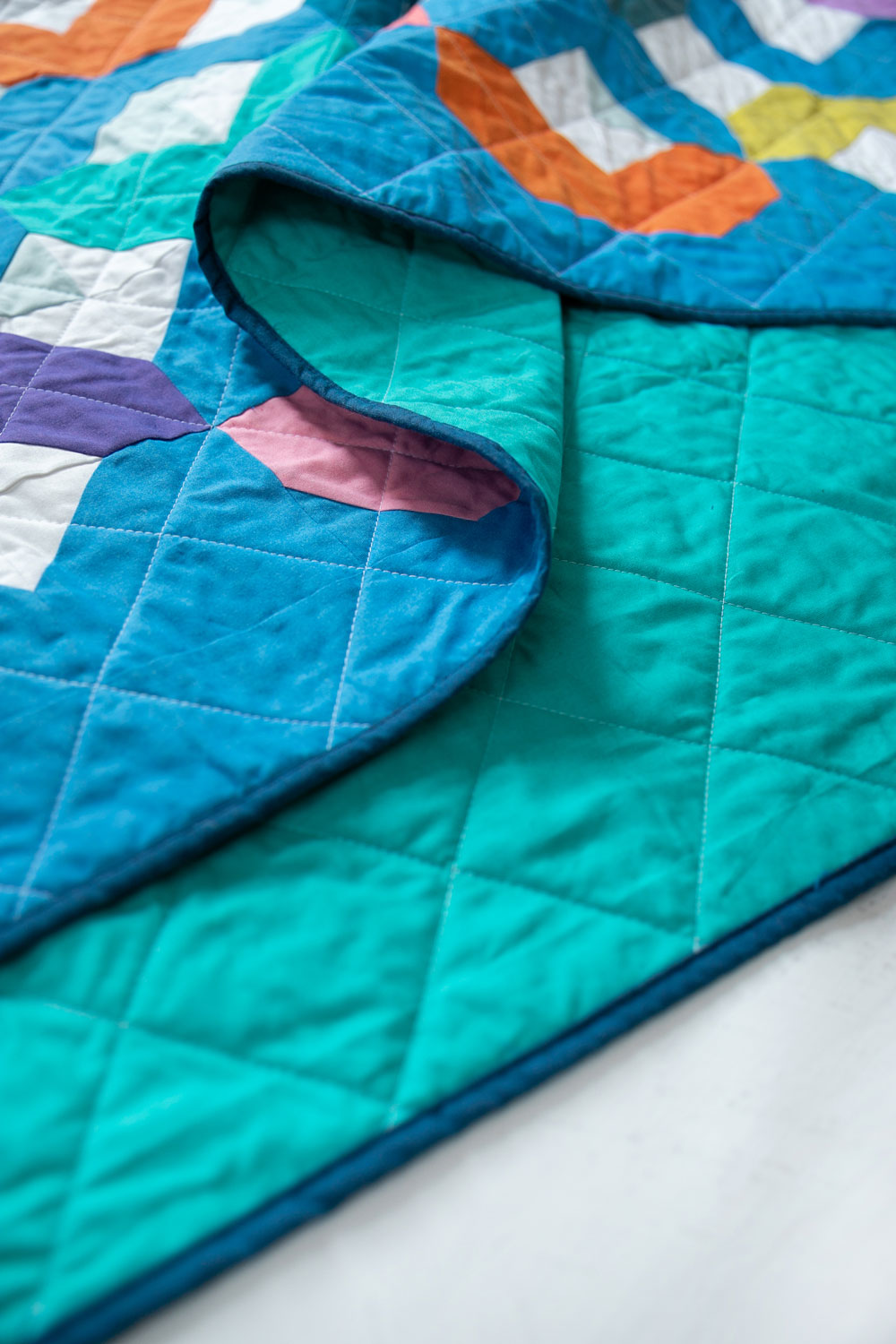 Make a Rainbow Quilt using this simple alteration to the Glitter & Glow quilt pattern. This is fat quarter friendly and great for newbie quilters and beginners. suzyquilts.com #rainbowquilt #shotcotton