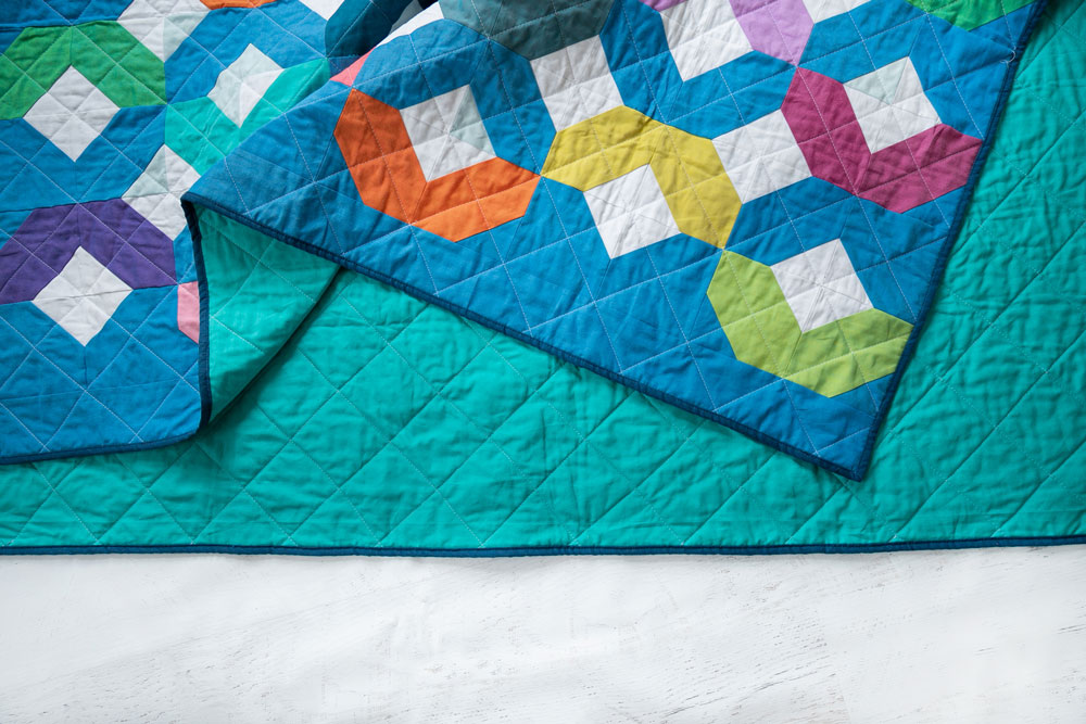 Make a Rainbow Quilt using this simple alteration to the Glitter & Glow quilt pattern. This is fat quarter friendly and great for newbie quilters and beginners. suzyquilts.com #babyquilt #rainbowbabyquilt