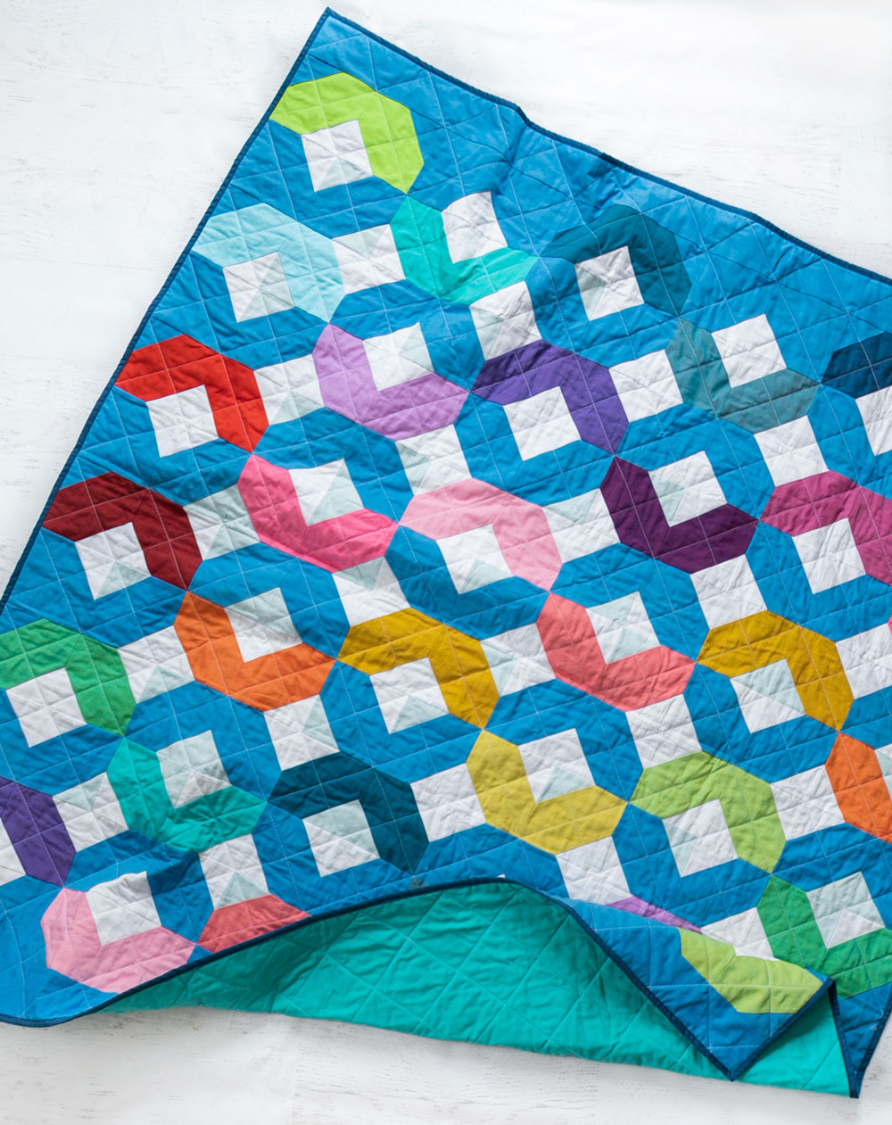 Make a Rainbow Quilt using this simple alteration to the Glitter & Glow quilt pattern. This is fat quarter friendly and great for newbie quilters and beginners. suzyquilts.com #rainbowquilt