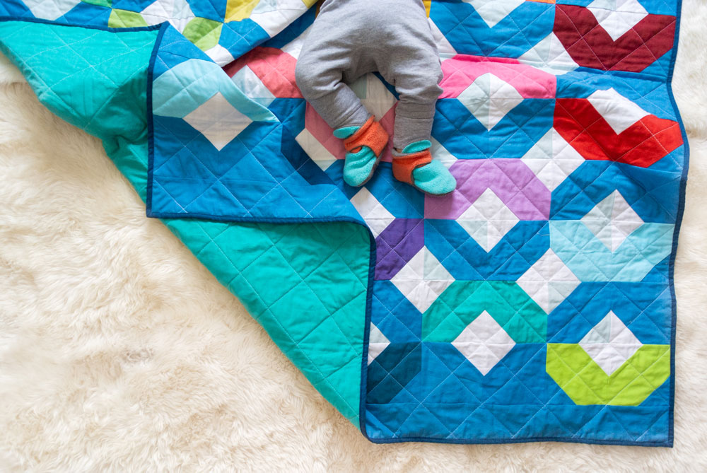 Make a Rainbow Quilt using this simple alteration to the Glitter & Glow quilt pattern. This is fat quarter friendly and great for newbie quilters and beginners. suzyquilts.com #rainbowquilt #rainbowbabyquilt