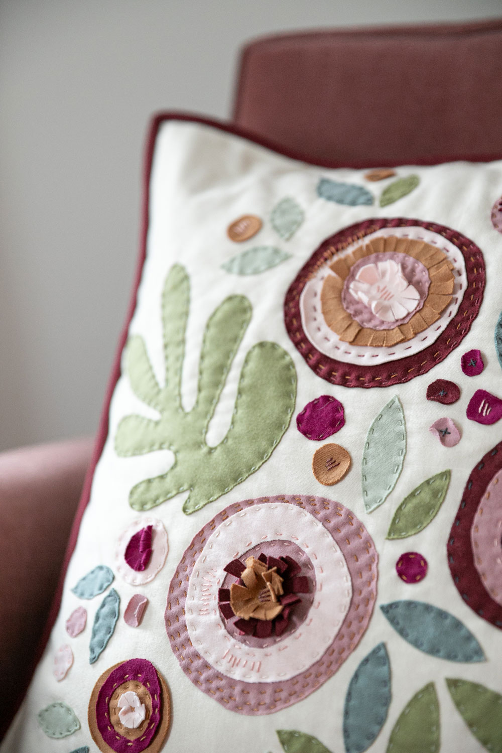 Make a modern appliqué pillow with knits! By using templates from the Bohemian Garden quilt pattern, you can create a buttery soft handmade pillow. suzyquilts.com #applique