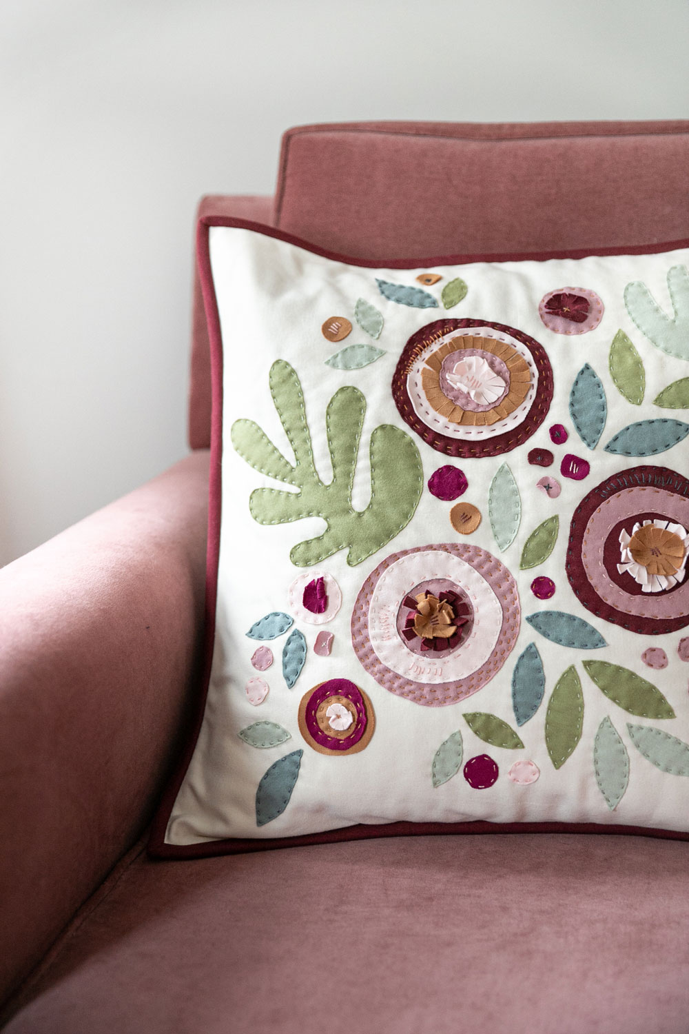 Make a modern appliqué pillow with knits! By using templates from the Bohemian Garden quilt pattern, you can create a buttery soft handmade pillow. suzyquilts.com #quiltedpillow