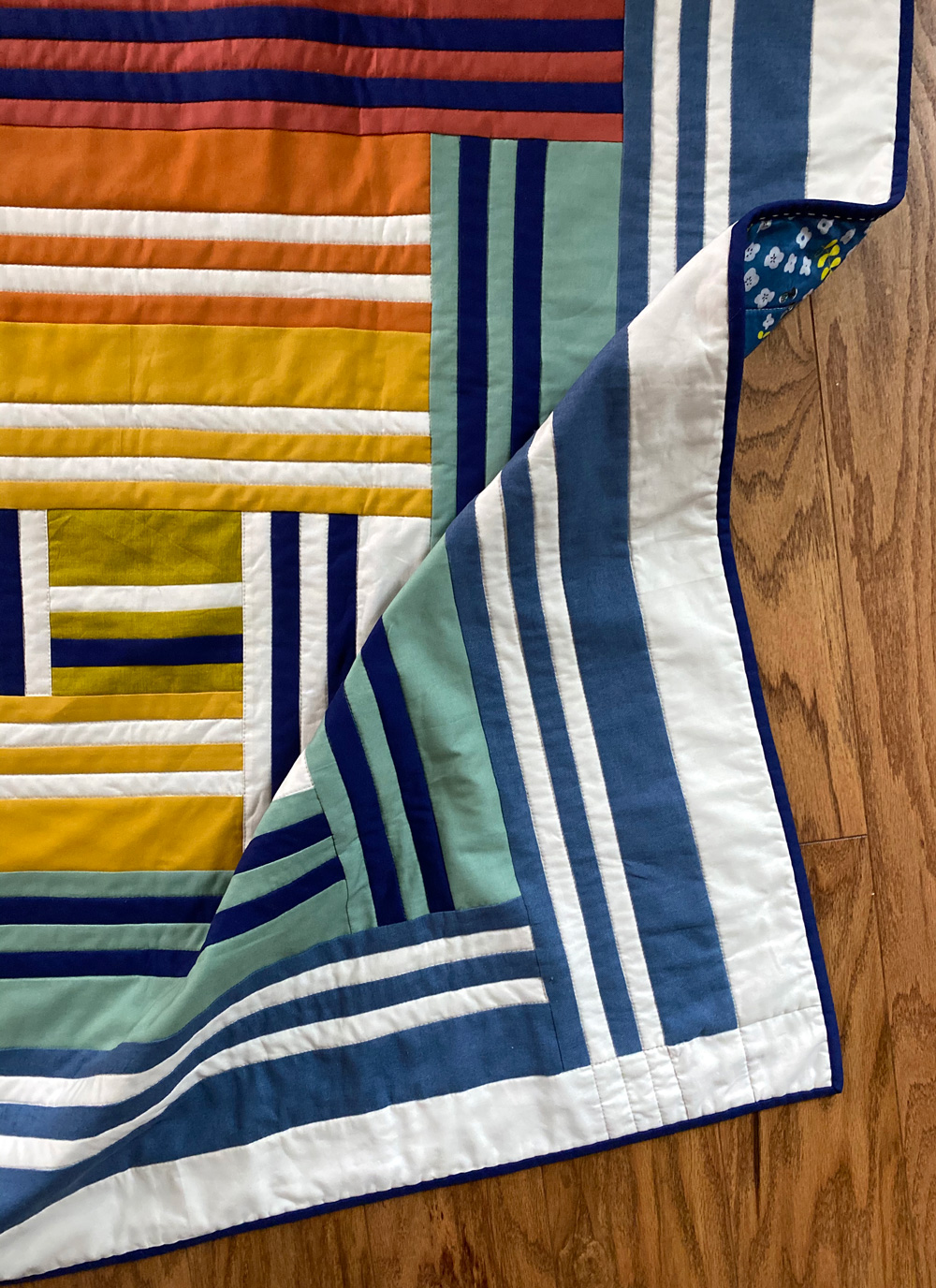 The Grow quilt pattern focuses on strip piecing – a simple quilting technique that creates a beautiful modern design. Beginner Friendly quilt pattern. See lots of quilt examples! suzyquilts.com #rainbowquilt