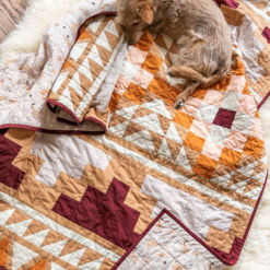 Be inspired by colors of the desert and make your own Mayan Mosaic quilt. With warm solid fabrics, this quilt pattern looks modern and timeless. With an Aztec design, this quilt kit creates a beautiful quilt! suzyquilts.com #quiltkit #dogquilt #quiltpattern
