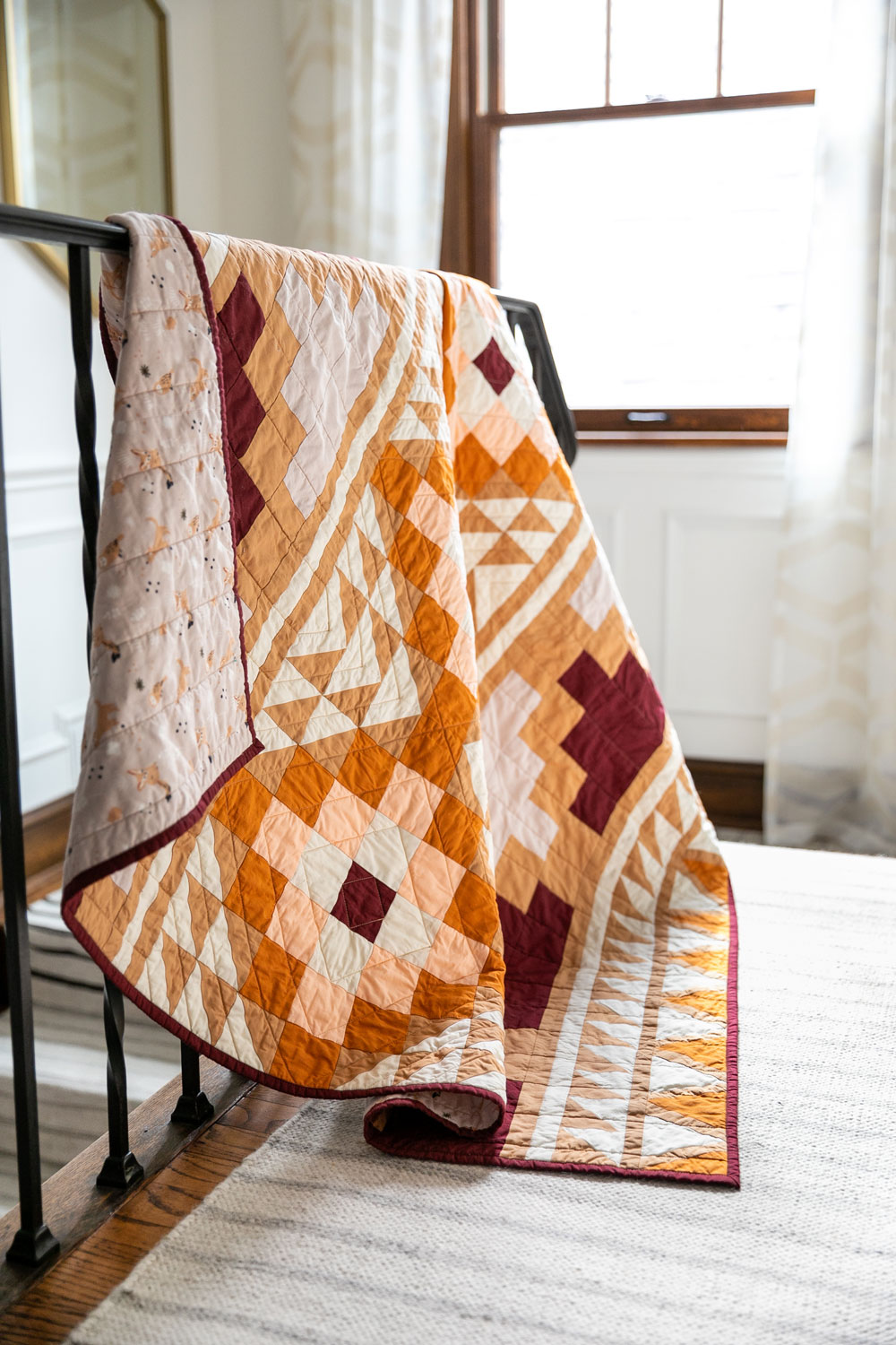 Be inspired by colors of the desert and make your own Mayan Mosaic quilt. With warm solid fabrics, this quilt pattern looks modern and timeless. With an Aztec design, this quilt kit creates a beautiful quilt! suzyquilts.com #quiltkit #aztecquilt #quiltpattern