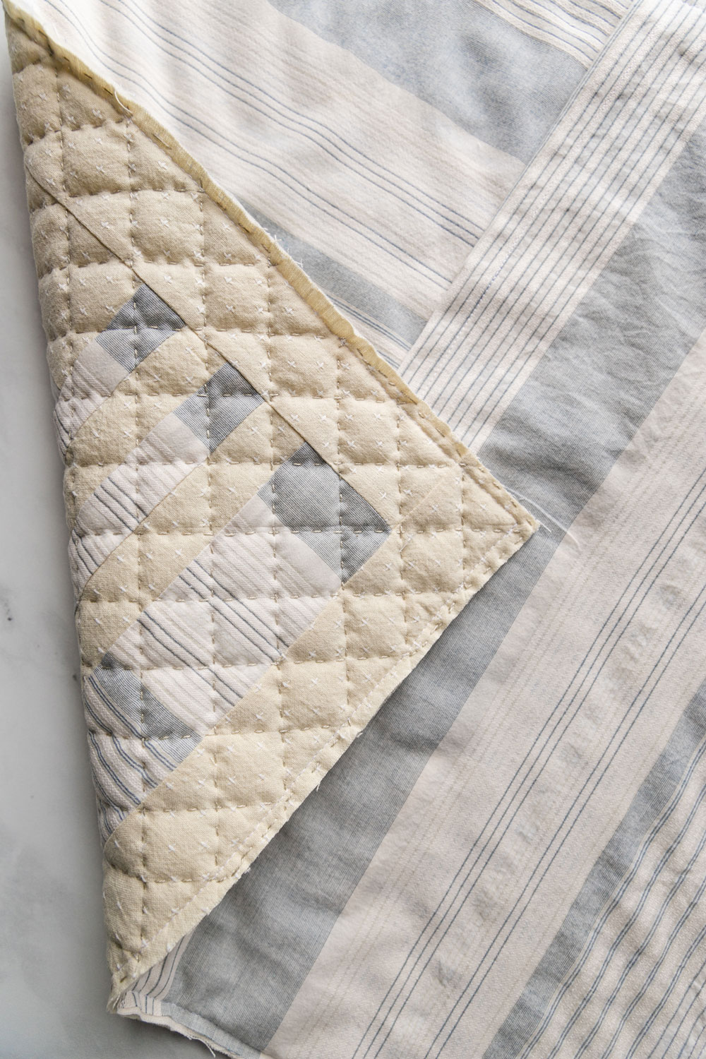 In this easy, beginner friendly quilting tutorial you will make a beautiful pillow with a simple envelope pillow cover. At the end there will be an option to finish the quilted pillow with binding | suzyquilts.com #quiltedpillow
