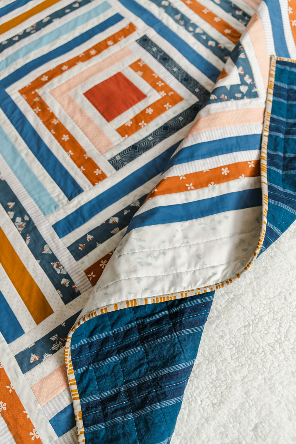 Sew a scrappy modern quilt with the Campfire quilt pattern. Based on the traditional log cabin quilt pattern, use long strips of fabric and scraps! suzyquilts.com #logcabinquilt #modernquilt