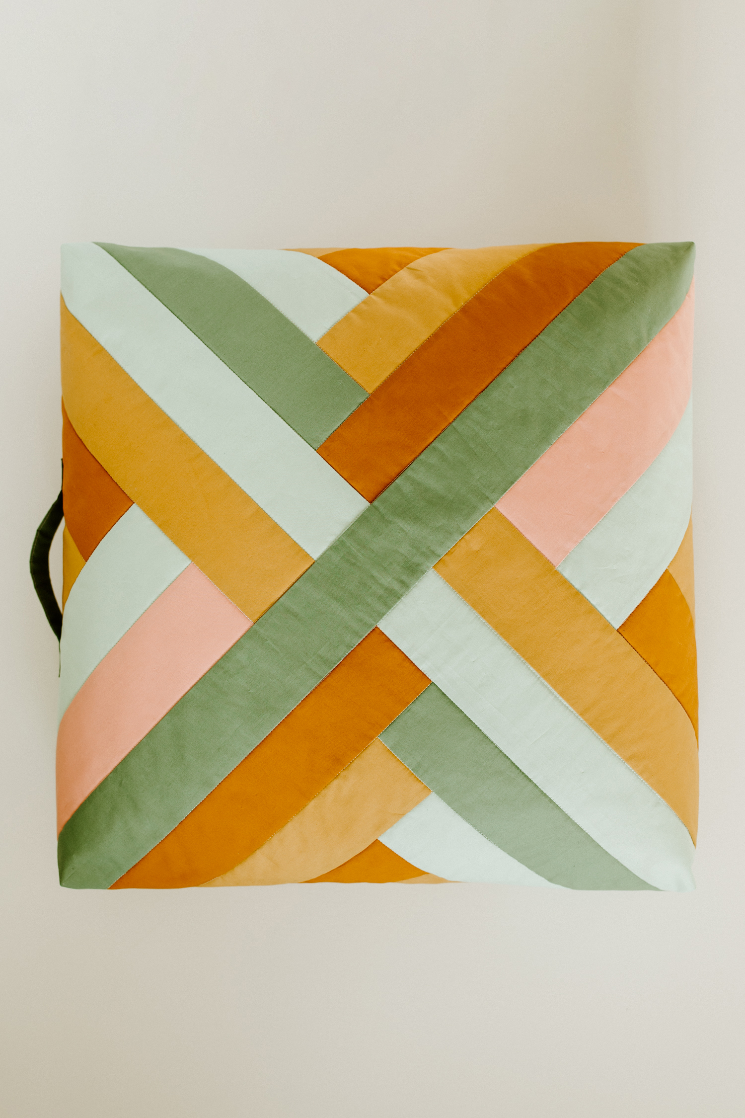 This quilted floor pillow tutorial walks you through step-by-step instructions to sew a floor pillow using the Maypole wall hanging pattern. suzyquilts.com #sewingtutorial #sewingdiy