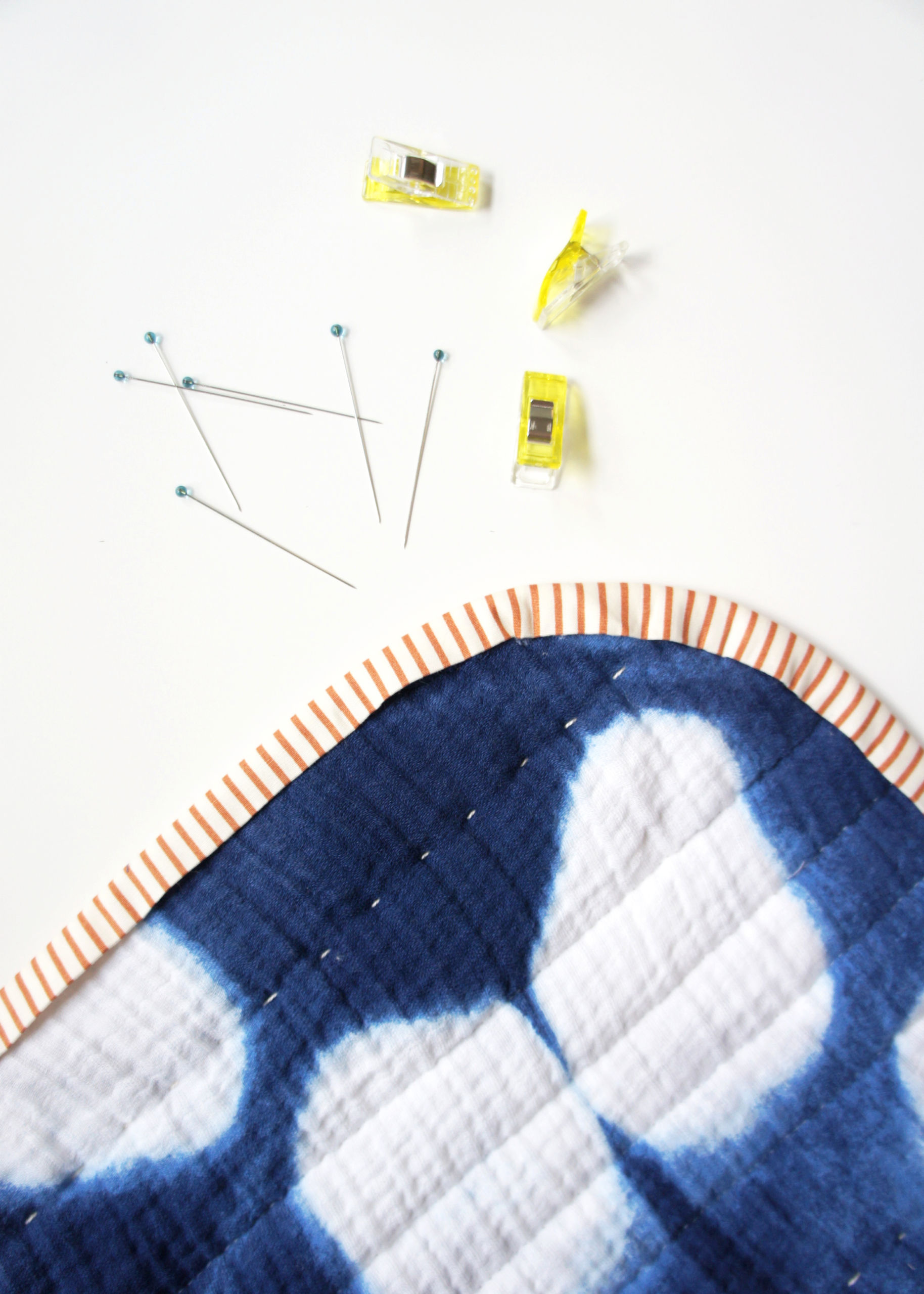 A step by step tutorial including photos and all the tools you need to get perfectly rounded quilt corners. Learn the best tips and tricks for rounding the corners of any quilt project and attaching a smooth binding. suzyquilts.com #sewingdiy #quilting