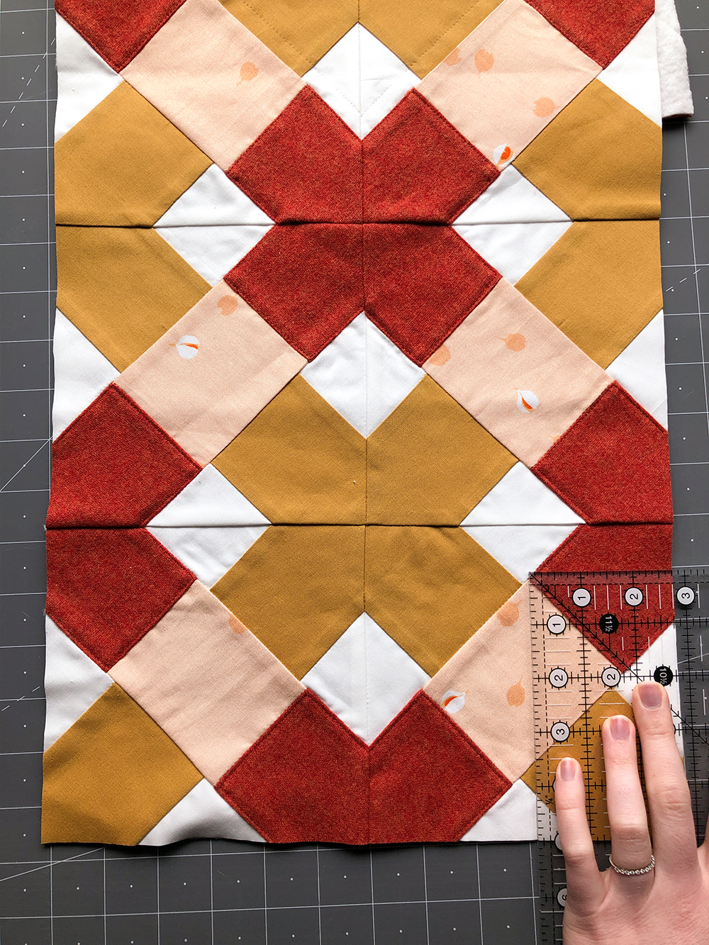 """Then, from each of the top corners, cut out a rectangle that measures 5"""" x 2 ¾"""", using the two raw edges as two sides of the rectangles. The 5"""" side of the cut rectangle should be parallel to the 30"""" side of the panel. This will create a flap for your lunch box that measures 6 ½"""" wide and 5"""" long. Check out the picture if you're more of a visual learner.  Repeat with your lining fabric so that you have a quilted panel and lining that are the same size and shape."""